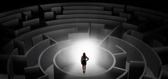 Kvinna som väljer mellan ingångar i en mitt av en mörk labyrint Royaltyfri Foto