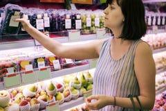 Kvinna som väljer några druvor på supermarket arkivfoton