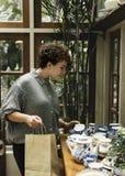 Kvinna som väljer några krukmakeriprodukter för garnering Arkivbilder