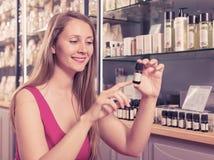 Kvinna som väljer nödvändig olja Royaltyfria Foton