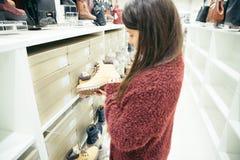 Kvinna som väljer nya kängor i shoppa Royaltyfri Bild