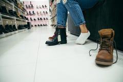 Kvinna som väljer nya kängor i shoppa Arkivbilder