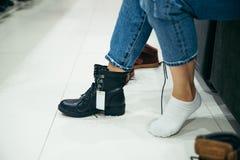 Kvinna som väljer nya kängor i shoppa Royaltyfria Foton