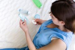 Kvinna som väljer produkter för en skincare Arkivfoton