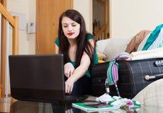 Kvinna som väljer semesterorten på internet Arkivbild