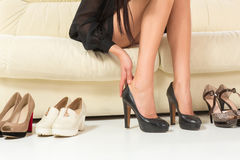 Kvinna som väljer skor eller problem med höga häl shopping arkivbild