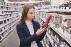 Kvinna som väljer skor i shoppa Fotografering för Bildbyråer