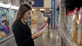 Kvinna som väljer tvätteritvättmedel i livsmedelsbutik Affärskvinna i supermarket arkivfoton