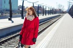 Kvinna som väntar ett drev på stationen Arkivbild