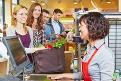 Kvinna som väntar i linje på supermarketkontrollen royaltyfri bild