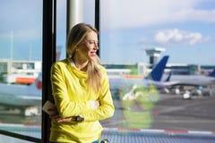 Kvinna som väntar på hennes flyg i flygplats arkivfoto