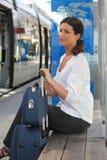 Kvinna som väntar på spårvagnstationen Arkivbild