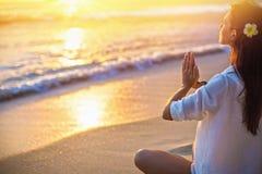 Kvinna som ?va Lotus Pose p? stranden royaltyfria foton