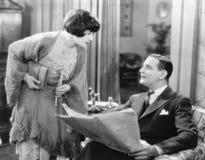 Kvinna som över böjer för att tala till en man som rymmer en tidning (alla visade personer inte är längre uppehälle, och inget go Arkivfoto