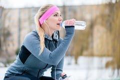Kvinna som vilar från att jogga eller sport på vinterdag Arkivfoto