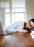 Kvinna som vilar huvudet på armen som stirrar på bärbar datorskärmen royaltyfri fotografi
