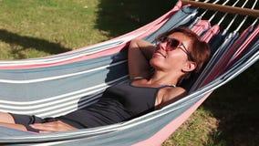 Kvinna som vilar i en hängmatta lager videofilmer