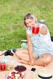 Kvinna som vilar i en picknick I händerna av en smoothie av vattenmelon Fotografering för Bildbyråer