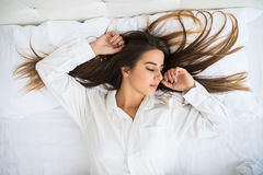 Kvinna som vilar i säng med händer bredvid hennes huvud på kudden royaltyfria foton