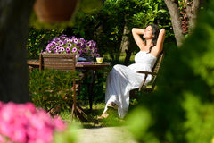 Kvinna som vilar i trädgård på sommar Fotografering för Bildbyråer