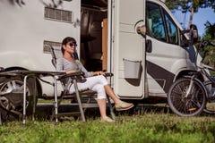 Kvinna som vilar nära motorhomes i natur Lopp för familjsemester, Arkivfoton