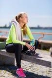 Kvinna som vilar, når att ha gjort sportar utomhus fotografering för bildbyråer