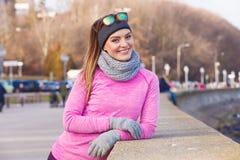 Kvinna som vilar, n?r att ha gjort sportar utomhus p? kall dag arkivfoton
