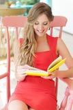 Kvinna som vilar och läser den favorit- boken royaltyfria bilder