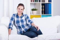 Kvinna som vilar på en soffa royaltyfria foton