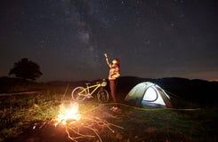 Kvinna som vilar på natten som mycket campar nära lägereld, turist- tält, cykel under aftonhimmel av stjärnor arkivfoto
