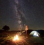Kvinna som vilar på natten som mycket campar nära lägereld, turist- tält, cykel under aftonhimmel av stjärnor royaltyfri bild