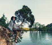 Kvinna som vilar på träd arkivbild