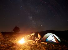 Kvinna som vilar p? natten som mycket campar n?ra l?gereld, turist- t?lt, cykel under aftonhimmel av stj?rnor royaltyfria bilder