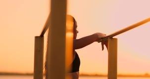 Kvinna som vilar stundanseende i solnedgångstången nära den bakre sikten En härlig brunettkvinna med långa hårställningar nära arkivfilmer