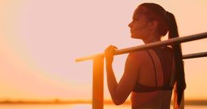 Kvinna som vilar stundanseende i solnedgångstången nära den bakre sikten En härlig brunettkvinna med långa hårställningar nära lager videofilmer