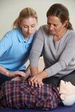 Kvinna som visar CPR på utbildningsattrapp i första hjälpengrupp Royaltyfria Bilder