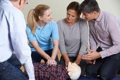 Kvinna som visar CPR på utbildningsattrapp i första hjälpengrupp Arkivbilder