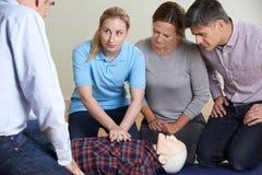 Kvinna som visar CPR på utbildningsattrapp i första hjälpengrupp Royaltyfri Fotografi