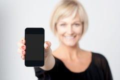Kvinna som visar den nya telefonen i marknad Arkivfoton