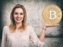 Kvinna som visar det guld- Bitcoin myntet Cryptocurrency Arkivfoto
