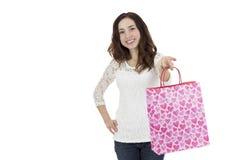 Kvinna som visar en pappers- gåvapåse Arkivbild