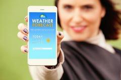 Kvinna som visar ett förutsett väder i en mobiltelefon app Arkivbild