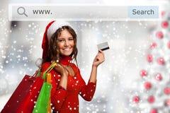 Kvinna som visar hennes kreditkort, medan shoppa för jul Arkivfoto