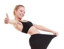 Kvinna som visar hur mycket vikt henne som är borttappad, stora flåsanden Arkivbild