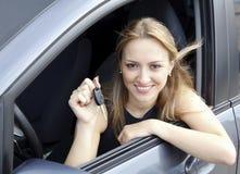 Kvinna som visar tangenten av henne den nya bilen. Arkivfoton