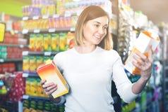 Kvinna som väljer uppfriskande drycker i supermarket Royaltyfri Fotografi