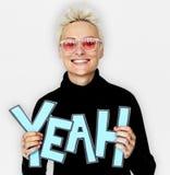 Kvinna som Yeah ler ståenden för ord för lycka den hållande komiska royaltyfri fotografi