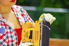 Kvinna sombär arbete handskar, tar bort sandpapper från den elektriska slipmaskinen Royaltyfria Bilder