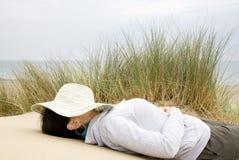 Kvinna sovande på strandlandskap Arkivfoton