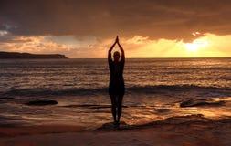 Kvinna Tadasana - berget poserar yoga vid havet på soluppgång royaltyfri bild